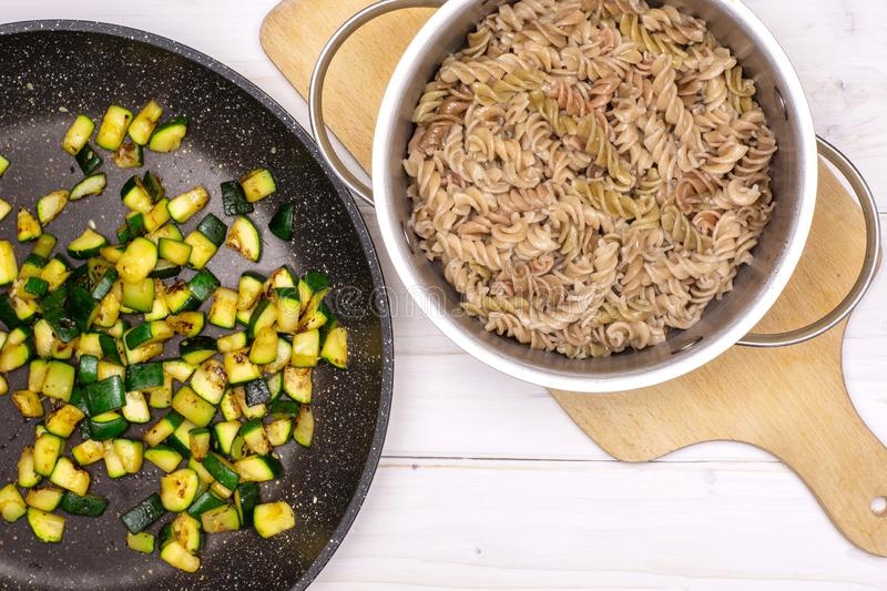 Fusilli pasta with zucchini on grey wood stock photography