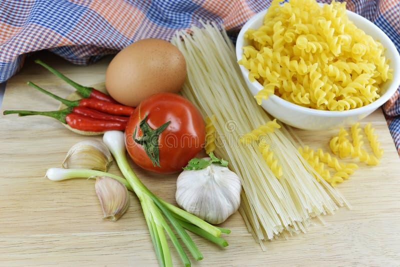 Fusilli, spagetti, vitlök, chili, lök, ägg och tomat på w royaltyfri foto