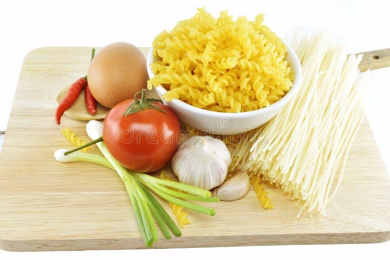 Fusilli, spagetti, vitlök, chili, lök, ägg och tomat på w royaltyfria bilder