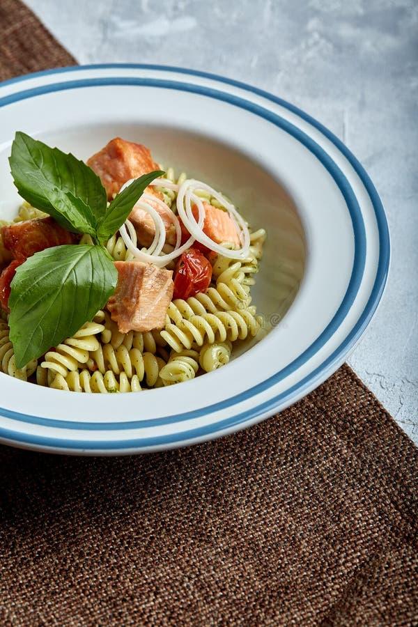 Fusilli-Teigwaren mit gebackenen Lachsen und Spinat Das Konzept der italienischen Küche, klassisch Schön eingemachte Tabelle mit stockfotografie