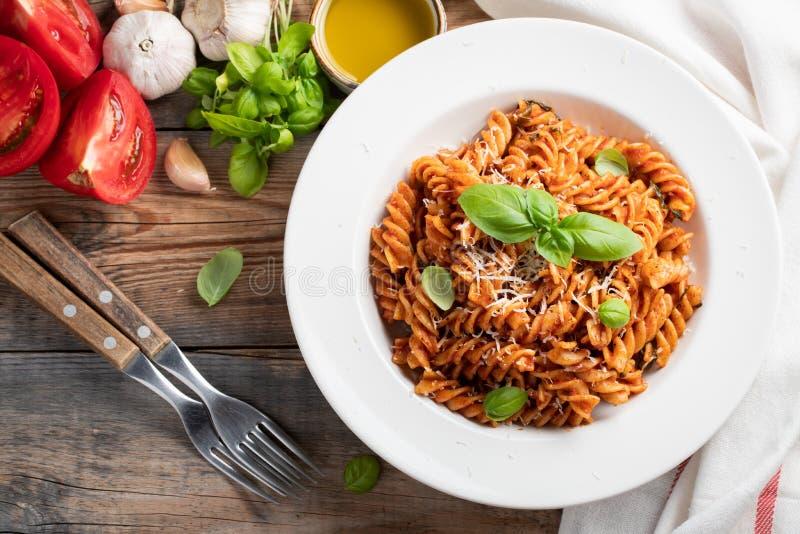 Fusilli-Teigwaren mit Tomatensauce, Knoblauch, Basilikum- und Parmesankäseparmesankäse auf einem alten Holztisch Beschneidungspfa stockfotos