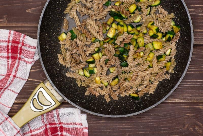 Fusilli-Teigwaren mit Zucchini auf braunem Holz stockbild