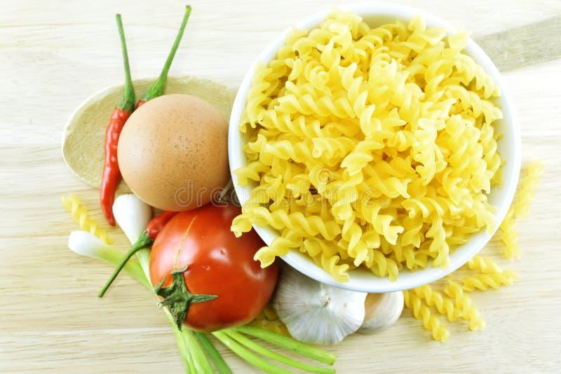Fusilli, vitlök, chili, lök, ägg och tomat på trä arkivbild