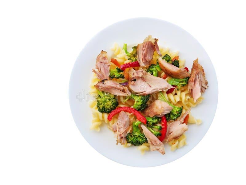 Fusillideegwaren met getrokken kippenvlees, broccoli en groenten op witte plaat stock foto's