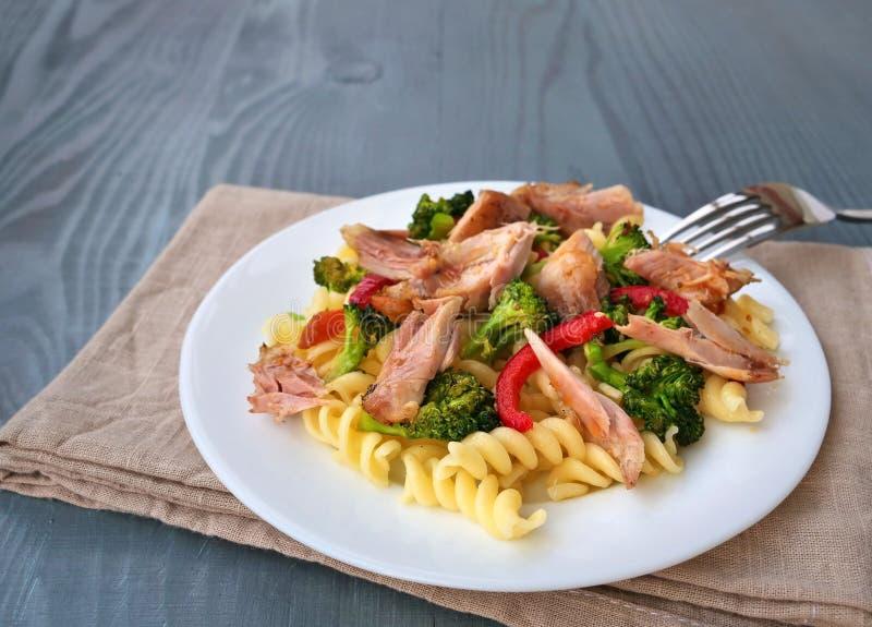 Fusillideegwaren met getrokken kippenvlees, broccoli en groenten op witte plaat stock afbeeldingen