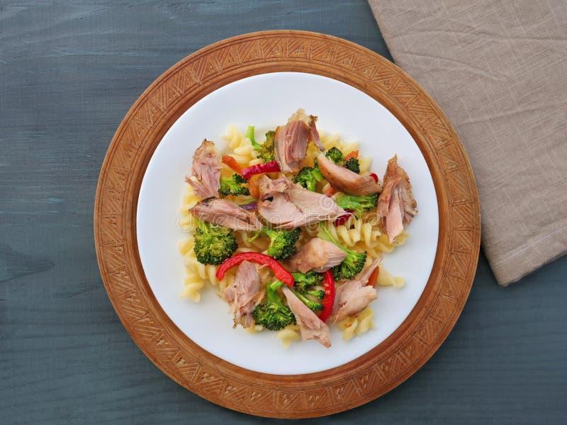 Fusillideegwaren met getrokken kippenvlees, broccoli en groenten op witte plaat stock afbeelding