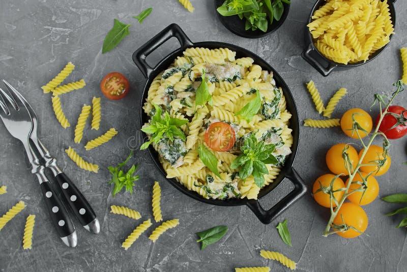 Fusillideegwaren met spinazie, kers, bacon in zwarte schotels royalty-vrije stock afbeeldingen
