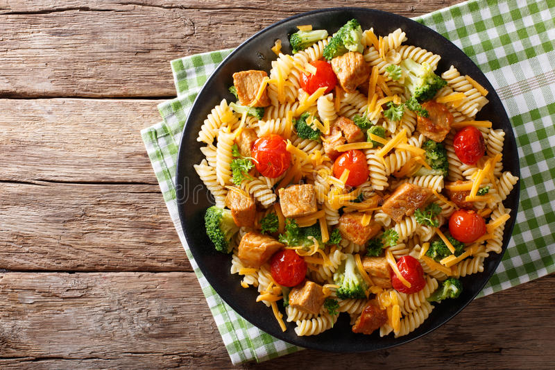 Fusillideegwaren met varkensvlees, broccoli, tomaten en kaascheddar c stock fotografie