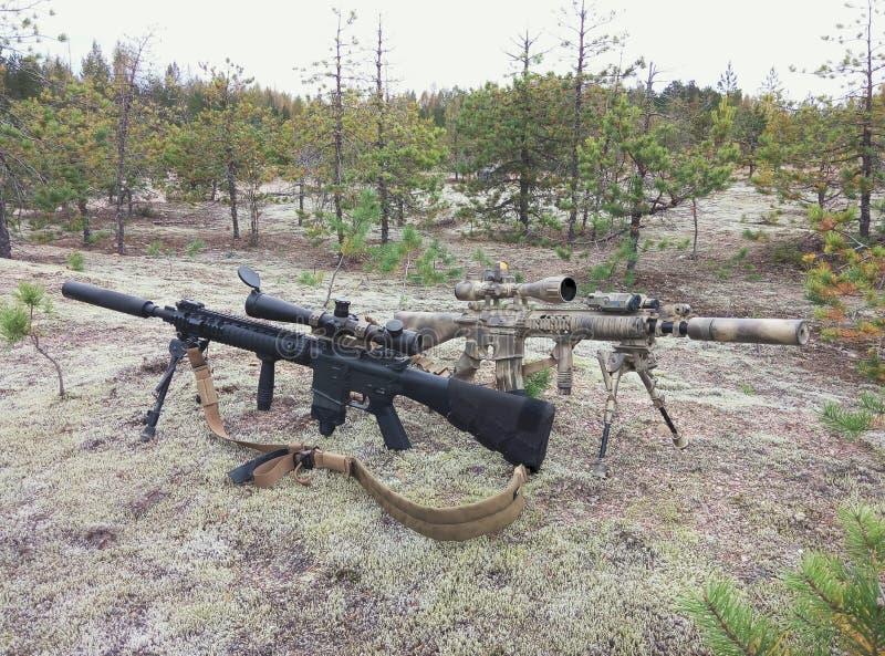 Fusils d'assaut sur le fond des forêts et du sable de pin Un des fusils peints dans la couleur de désert photographie stock