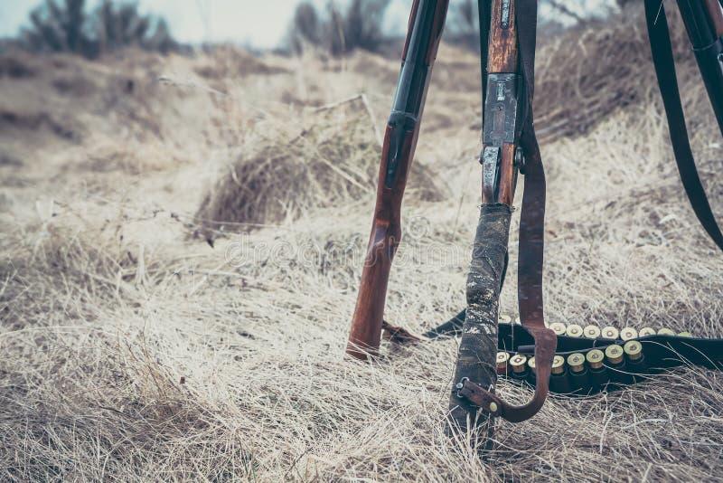 Fusils de chasse de chasse avec la ceinture de munitions sur l'herbe sèche comme fond de chasse photographie stock