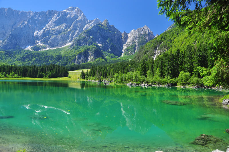 Crystal clear Fusine lake, Alpine scenery. Friuli, Italy. Crystal clear transparent green water, Fusine alpine lake, Friuli Venezia Giulia, Italy. Italian Alps stock photo