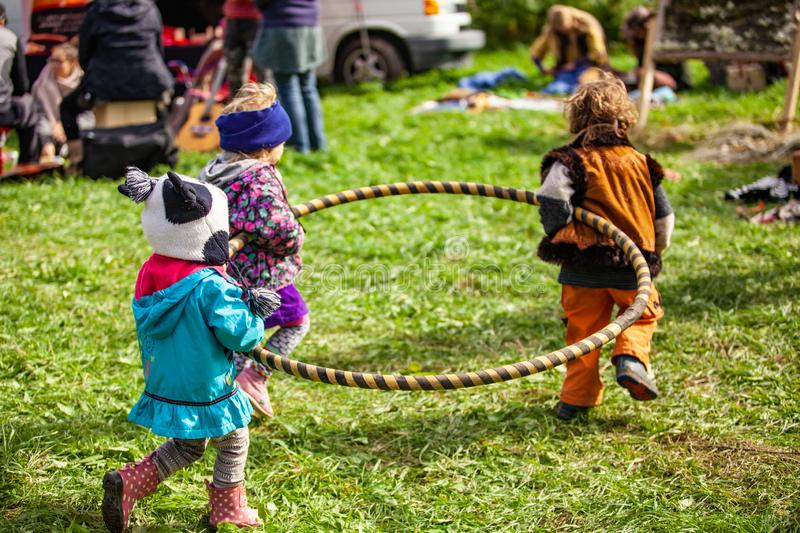 Fusion of cultural & modern music event. Three children are seen carrying a hula hoop through a campsite at a music festival, one boy wears a Native American stock image