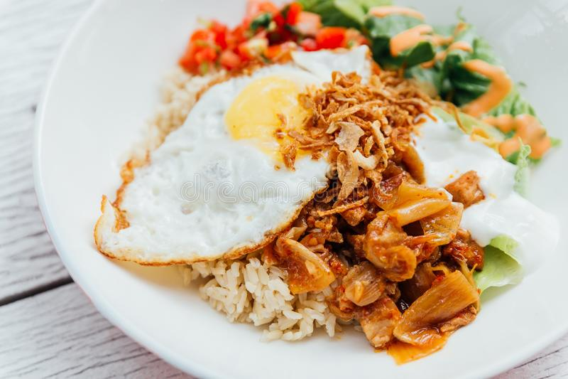 Fusion food Rice bowl toppings kimchi pork, organic fried egg, Korean eggplant and salad stock photography