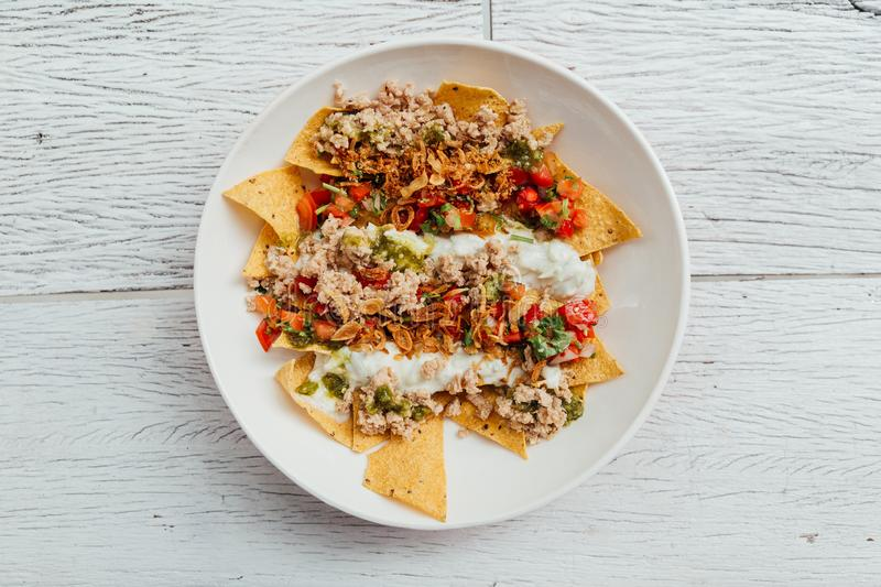 Fusion food: Top view of Soboro Chicken Nachos: Japanese-style stir-fried chicken with tomato salsa, yogurt. Fusion food: Top view of Soboro Chicken Nachos royalty free stock images
