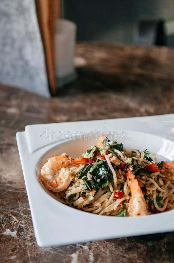 Fusion Pasta spicy Thai Pad Kapraw spaghetti with garlic, red chilli, shrimps and holy basil in white plate. On marble table royalty free stock image