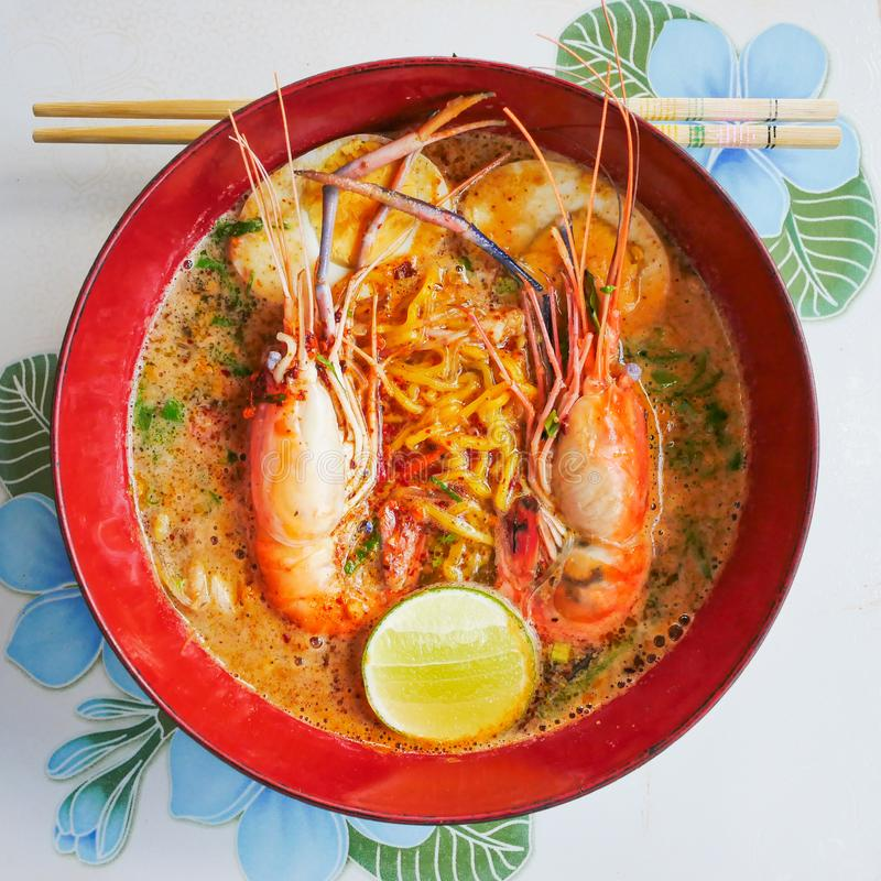 Fusion spicy thai-chinese food in thailand by top view, Tom yum koong-noodle in soup  with topping of shrimps boiled egg parsley. Onion and lemon in red bowl on stock images