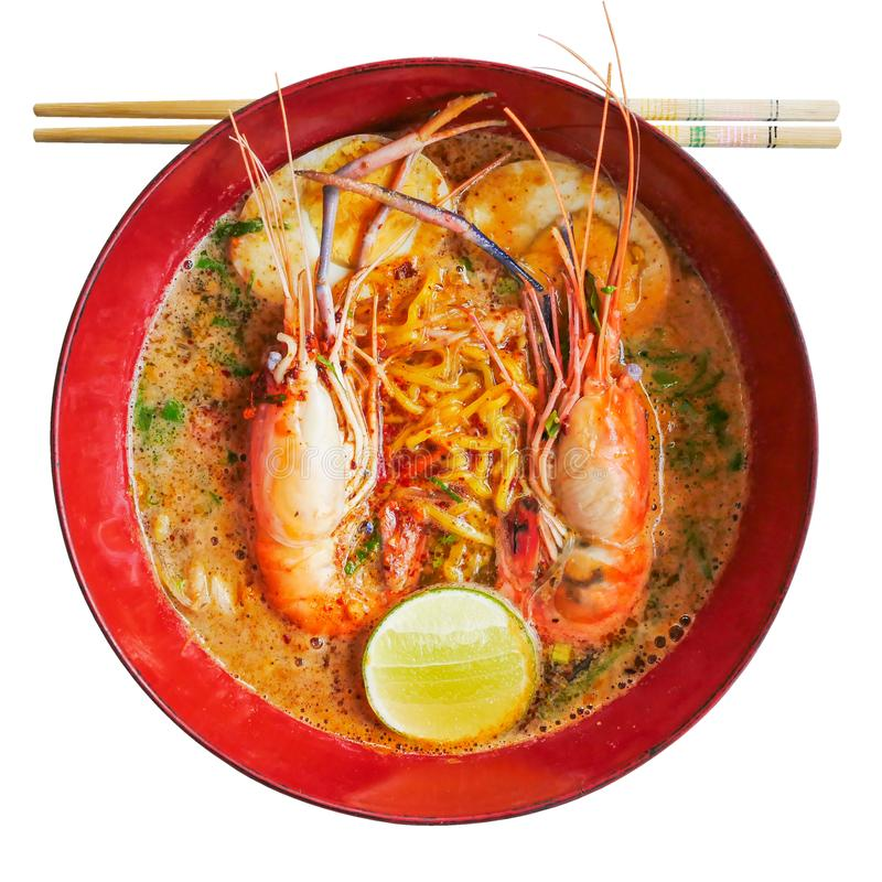 Isolated spicy thai-chinese food in thailand by top view, Tom yum koong-noodle in soup  with topping of shrimps boiled egg parsley. Isolated fusion spicy thai stock photos