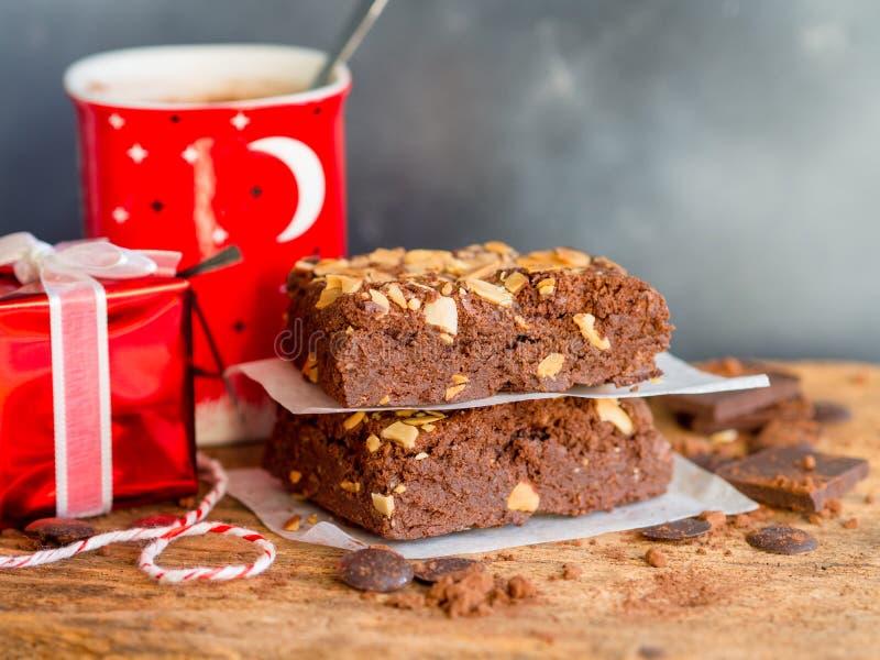 Fuska ihop den mörka chokladkakan för nissen med röd bakgrund för gåvaasken fotografering för bildbyråer
