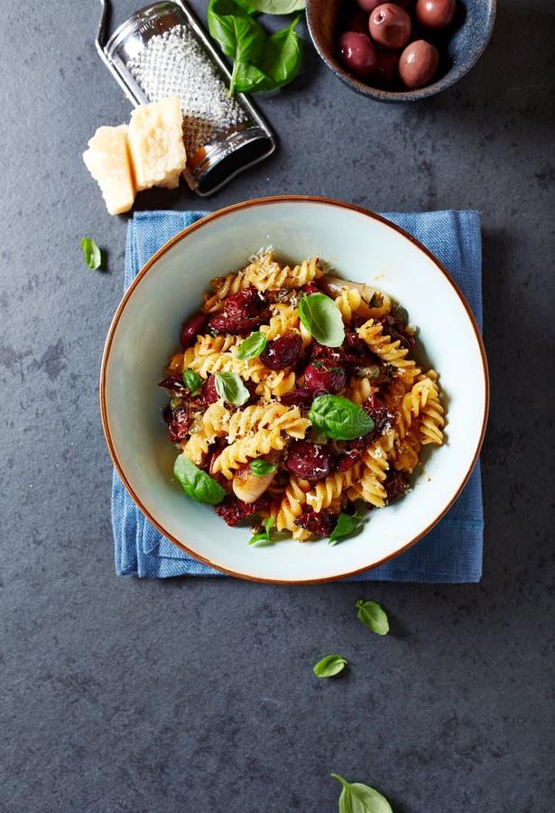 Fussili pasta med oliv, schalottenlökar, torkade tomater och parmesan royaltyfri bild