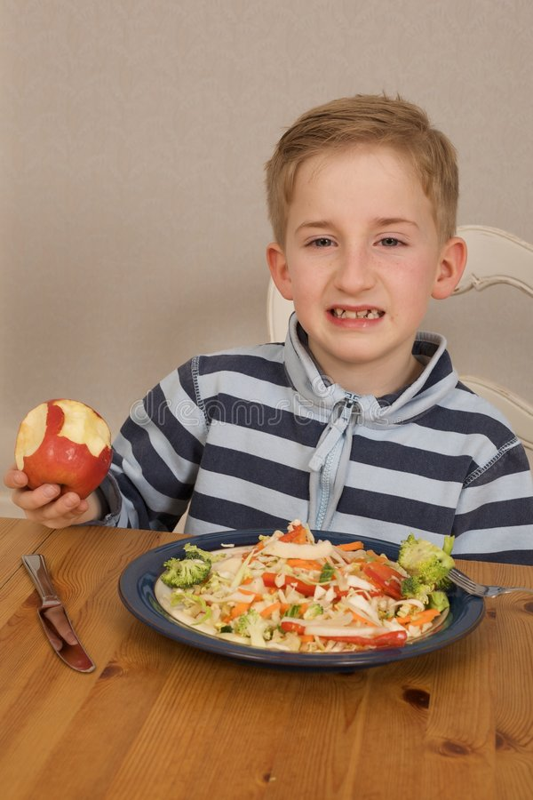 Fussy eater. Picture of a young boy who does not enjoy eating fruit and vegetables royalty free stock photo