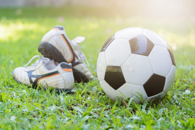 Futbol na zielonej trawy i stadniny bucie z słońcem zaświeca zdjęcia royalty free