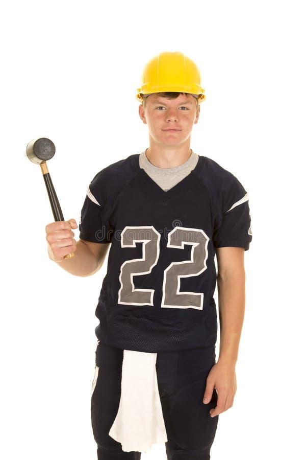 Futbolista con el casco y el martillo foto de archivo