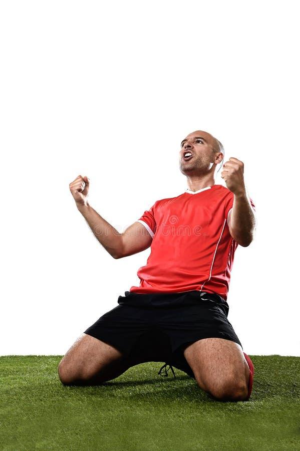 Futbolista feliz y emocionado en jersey rojo que celebra meta que anota que se arrodilla en echada de la hierba fotos de archivo