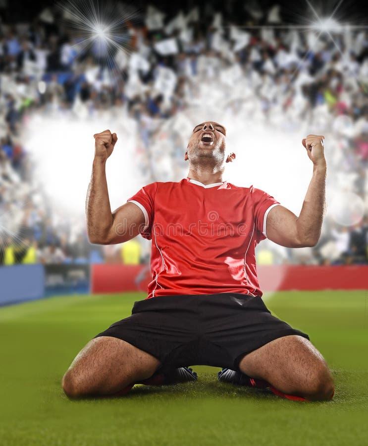 Futbolista feliz y emocionado en jersey rojo que celebra meta que anota que se arrodilla en echada de la hierba imagenes de archivo