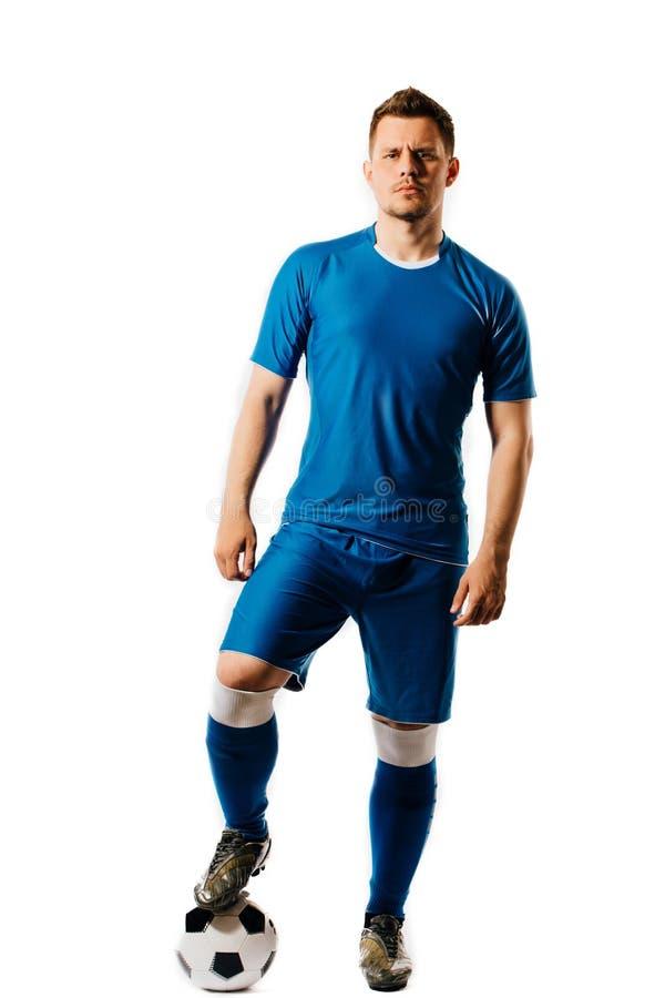 Futbolista hermoso joven con una presentación del balón de fútbol aislado en el fondo blanco foto de archivo