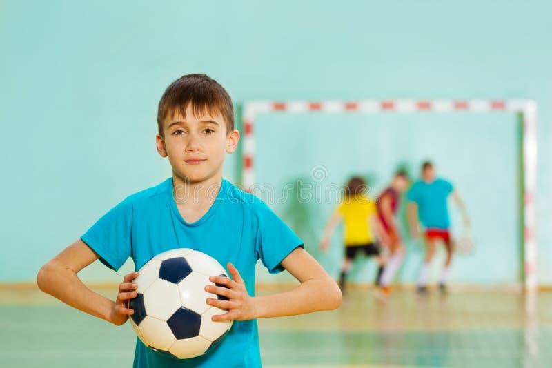 Futbolista joven listo para lanzar el balón de fútbol foto de archivo libre de regalías