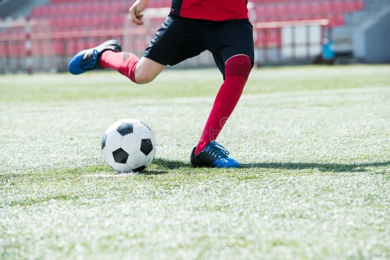 Futbolista joven que golpea la bola con el pie fotografía de archivo