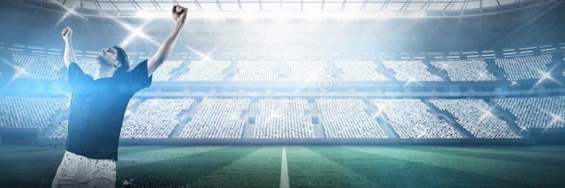Futbolista que celebra la victoria contra estadio contra el cielo fotos de archivo
