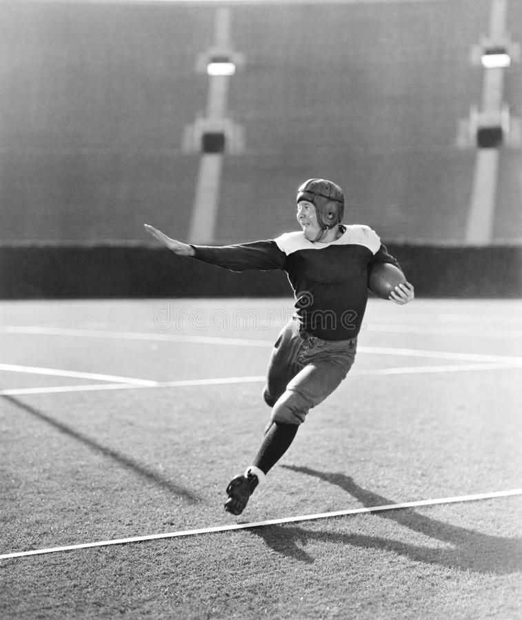 Futbolista que corre con la bola (todas las personas representadas no son vivas más largo y ningún estado existe Garantías del pr imagenes de archivo