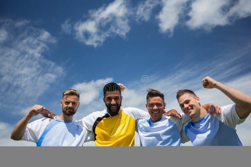 Futbolistas emocionados que se colocan así como el brazo alrededor foto de archivo