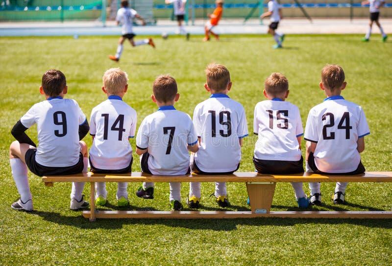 Futbolistas jovenes Fútbol joven Team Sitting en banco de madera foto de archivo libre de regalías