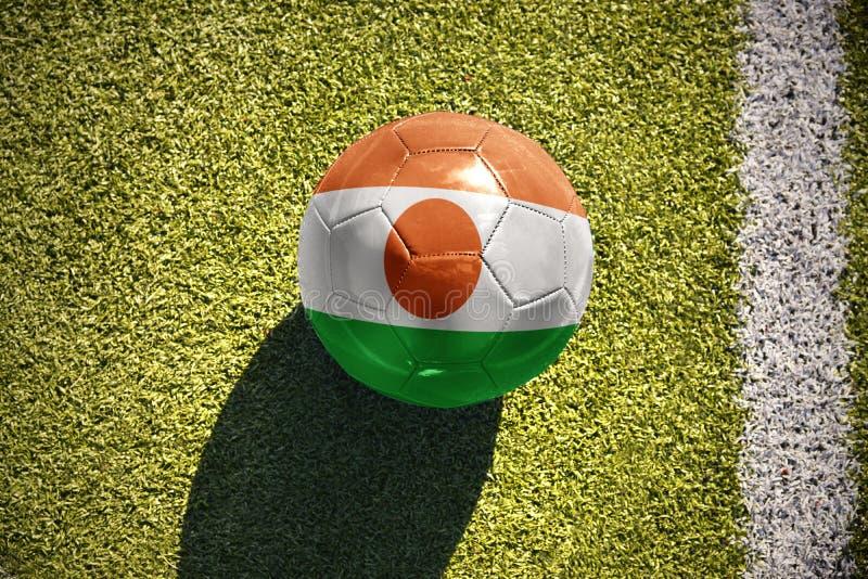 Futbolowa piłka z flaga państowowa Niger kłama na polu zdjęcie stock