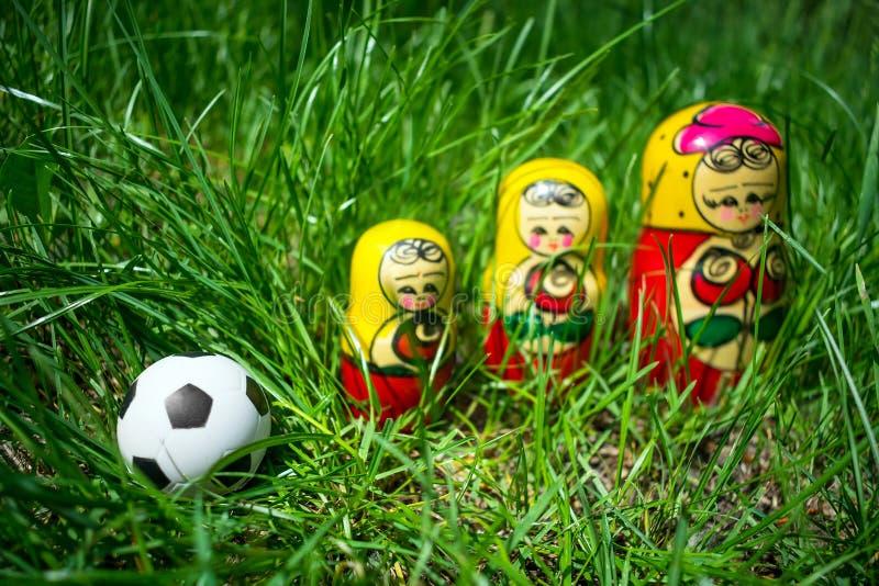 Futbolowa piłki nożnej piłka i trzy gniazdować lali w zieleni Zwycięzca, fotografia royalty free