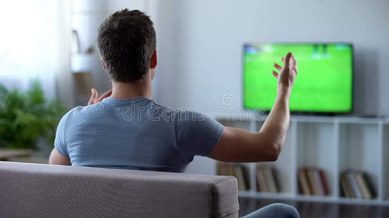 Futbolowy zwolennik aktywnie rozwesela jego ulubionej drużyny, rozczarowanej z grze obraz stock