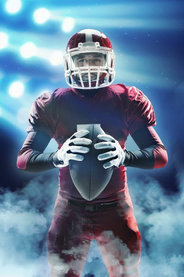 Futbolu amerykańskiego gracz pozuje z piłką na stadium tle fotografia stock