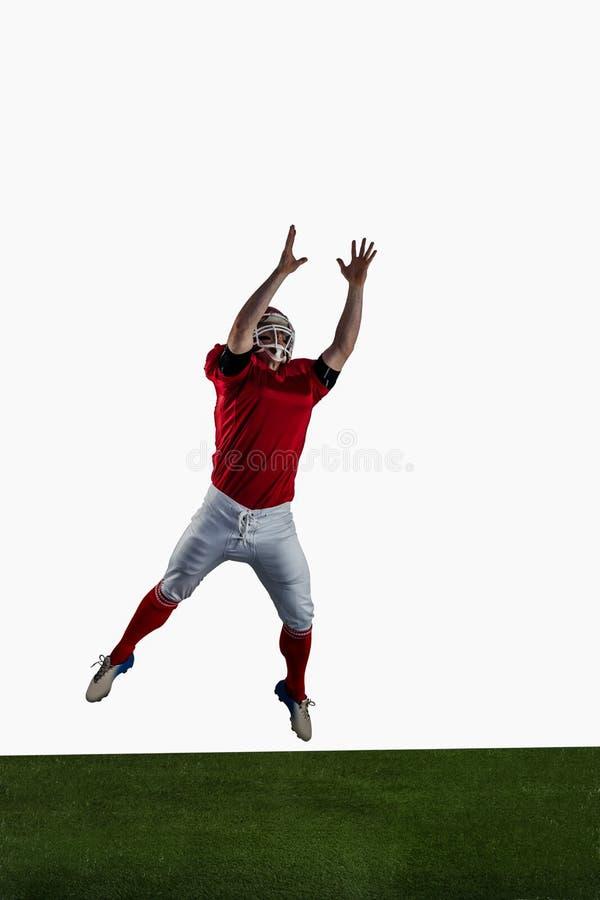 Futbolu amerykańskiego gracz próbuje łapać futbol fotografia stock