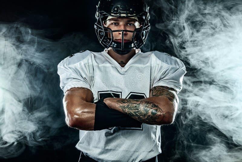 Futbolu amerykańskiego gracz, sportowiec w hełmie na czarnym tle z dymem Sporta i motywacji tapeta zdjęcia stock