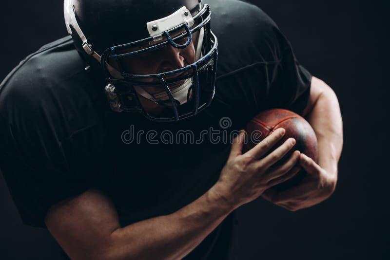 Futbolu amerykańskiego gracz z hełmem i zbroja z piłką przeciw czerni ścianie obraz royalty free