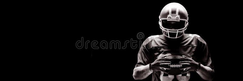 Futbolu amerykańskiego gracza pozycja z rugby piłką i hełmem fotografia stock