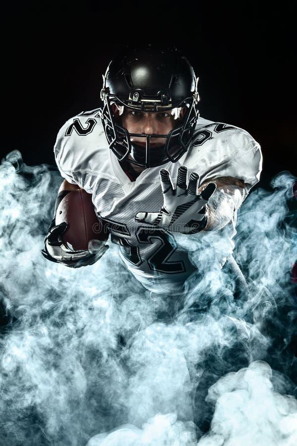 Futbolu amerykańskiego sportowa gracz w hełmie na czarnym tle z dymem Sporta i motywacji tapeta obrazy royalty free