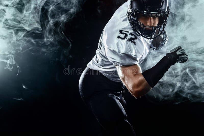 Futbolu amerykańskiego sportowa gracz w hełmie na czarnym tle z dymem Sporta i motywacji tapeta obraz stock