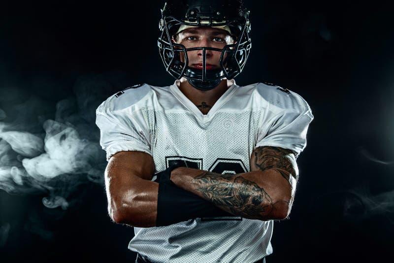Futbolu amerykańskiego sportowa gracz w hełmie na czarnym tle z dymem Sporta i motywacji tapeta zdjęcie stock