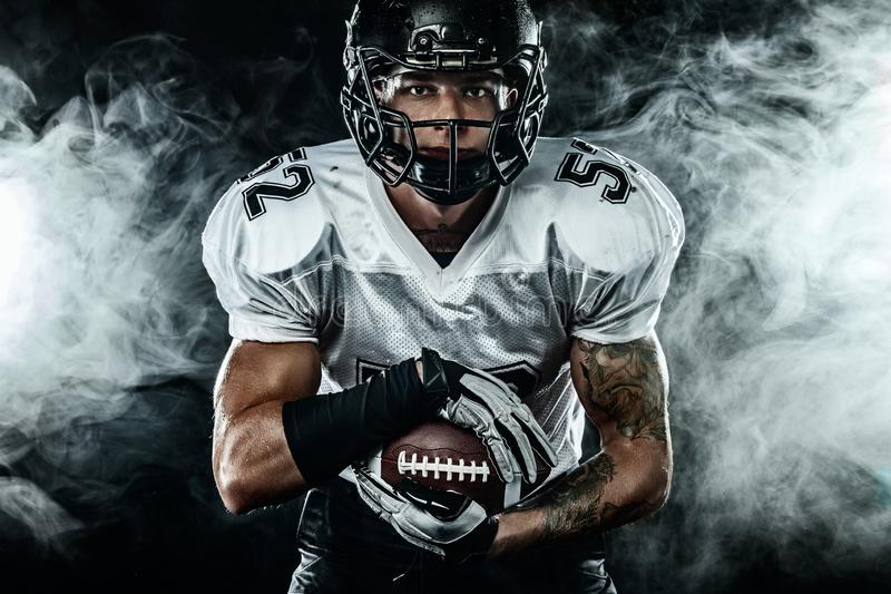Futbolu amerykańskiego sportowa gracz w hełmie na czarnym tle z dymem Sporta i motywacji tapeta fotografia royalty free