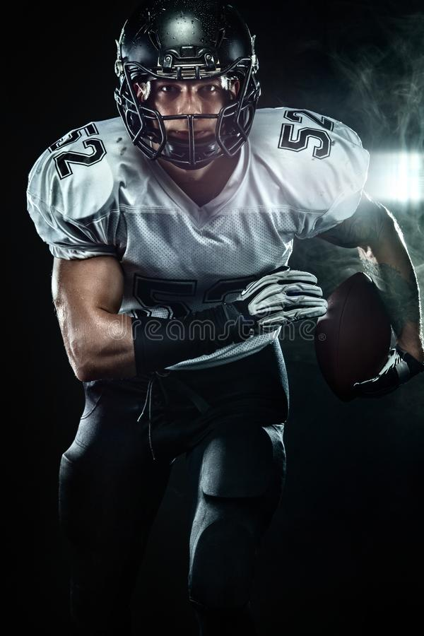 Futbolu amerykańskiego sportowa gracz w hełmie na czarnym tle z dymem Sporta i motywacji tapeta zdjęcie royalty free