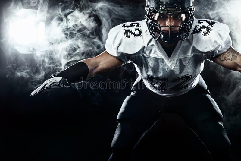 Futbolu amerykańskiego sportowa gracz w hełmie na czarnym tle z dymem Sporta i motywacji tapeta obraz royalty free