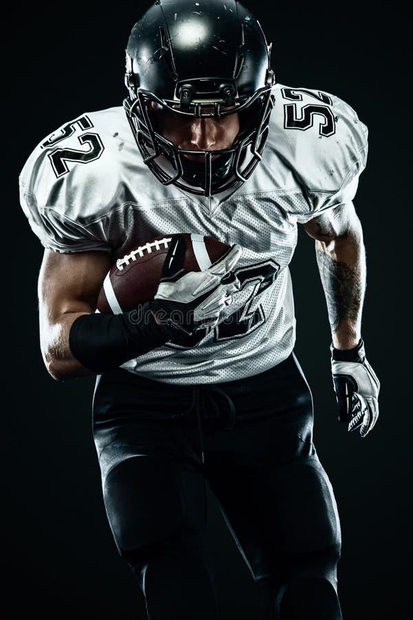 Futbolu amerykańskiego sportowa gracz w hełmie odizolowywał bieg w akcji na czarnym tle Sporta i motywacji tapeta fotografia stock